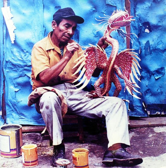 Pedro Linares sits crafting an alebrije--a magnificent red lizard with eagle's wings and a snake's mouth. Learn how to use this colorful Mexican folk art in your classroom.